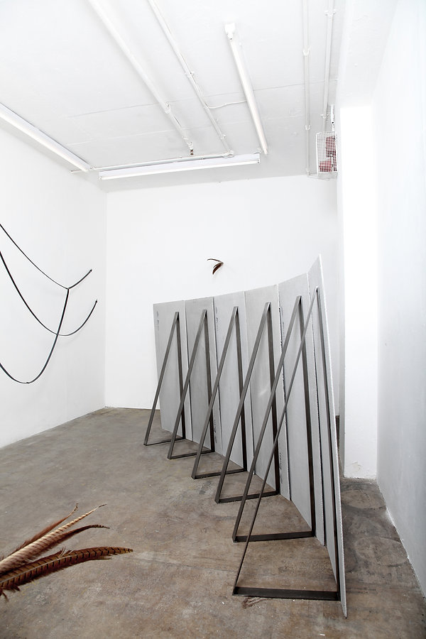 Simona Brinkmann, detail of exhibition view, Blank Stare Flat Hollow, solo show at Five Years, London. Ungrammatical Anatomies barrier sculpture, Arm's Length leather strap, feather sculptures, installation shot.