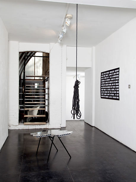 Simona Brinkmann,installation view, The Making at The Agency London,  Sacred Symmetries, aluminium tube parquet floor fragment, found tubular metal chair base, sculpture, contemporary art, incline floor, interior architectural fragments. Quick Grip, black shiny rubber tube rope, hanging sculpture. Text piece by Philippa Snow.
