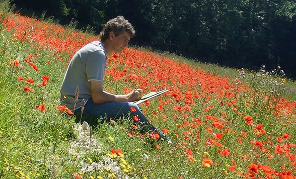 The artist Chris Bourne painting in a poppy field.