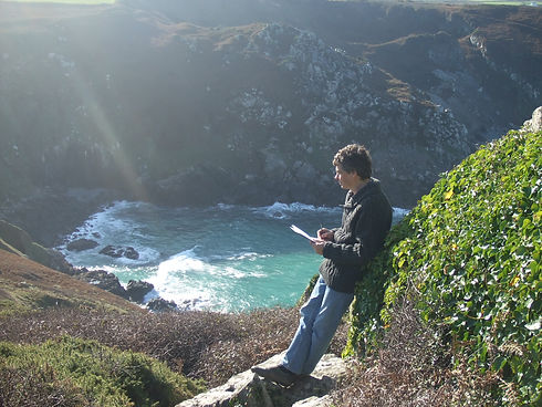 The artist Chris Bourne sketching above the sea on the rocky Cornish peninsula.