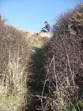 The artist Chris Bourne sketching sat on a Cornish boulder.