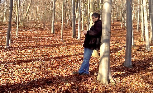 Artist Chris Bourne in autumn woods sketching for an artwork commission by Coworth Park Hotel, Ascot.