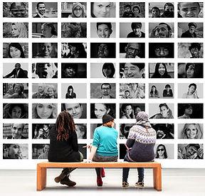 3 personnes assises sur un banc devant portraits