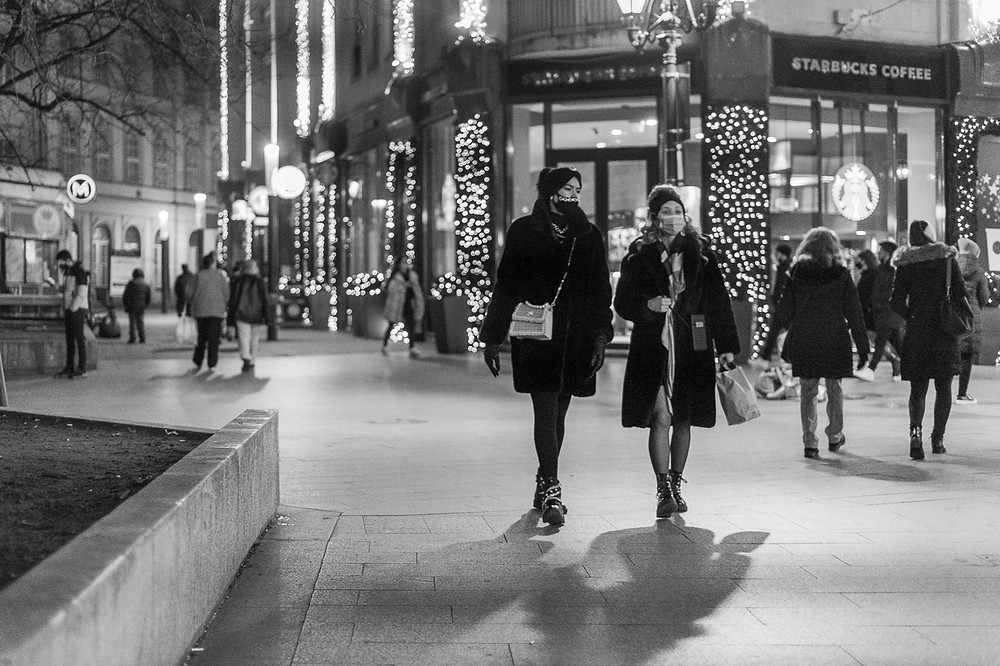 Two women walk down fashion high street in Budapest in black and white