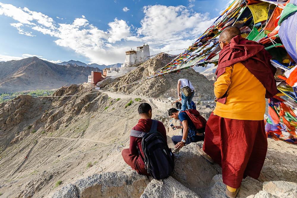 Buddhist monks overlooking Namgyal Tsemo Gompa in Leh Ladakh India