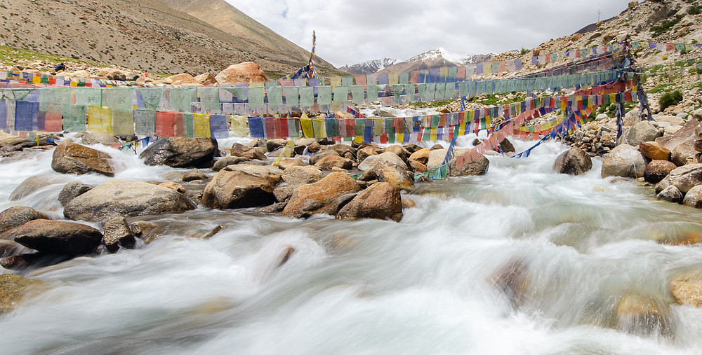 Long exposure shot of prayer flags over river in Ladakh north India