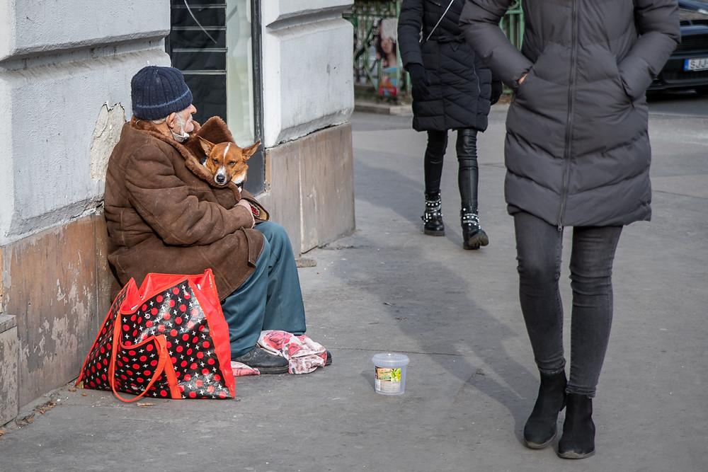 Homeless man tucks a corgi dog into his coat on side of street in Budapest