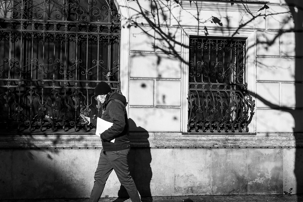 Black and white street photo of man walking past wall with shadows of tree branches