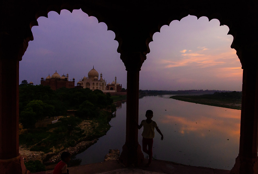 indian girl standing in front of sunset and taj mahal in agra india