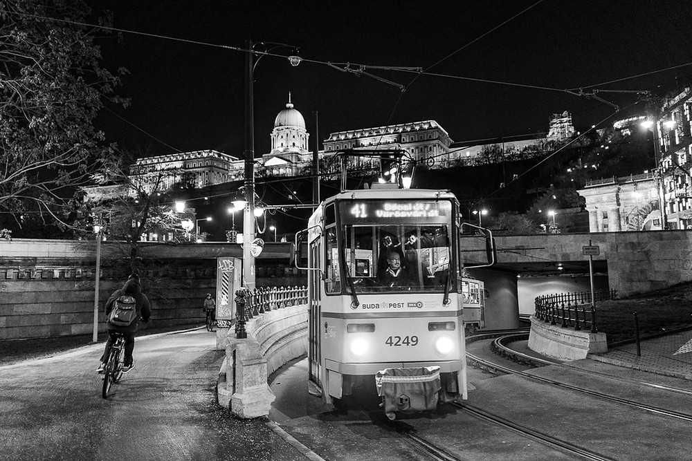 Black and white photo of tram and cyclist in Budapest, underneath the castle district