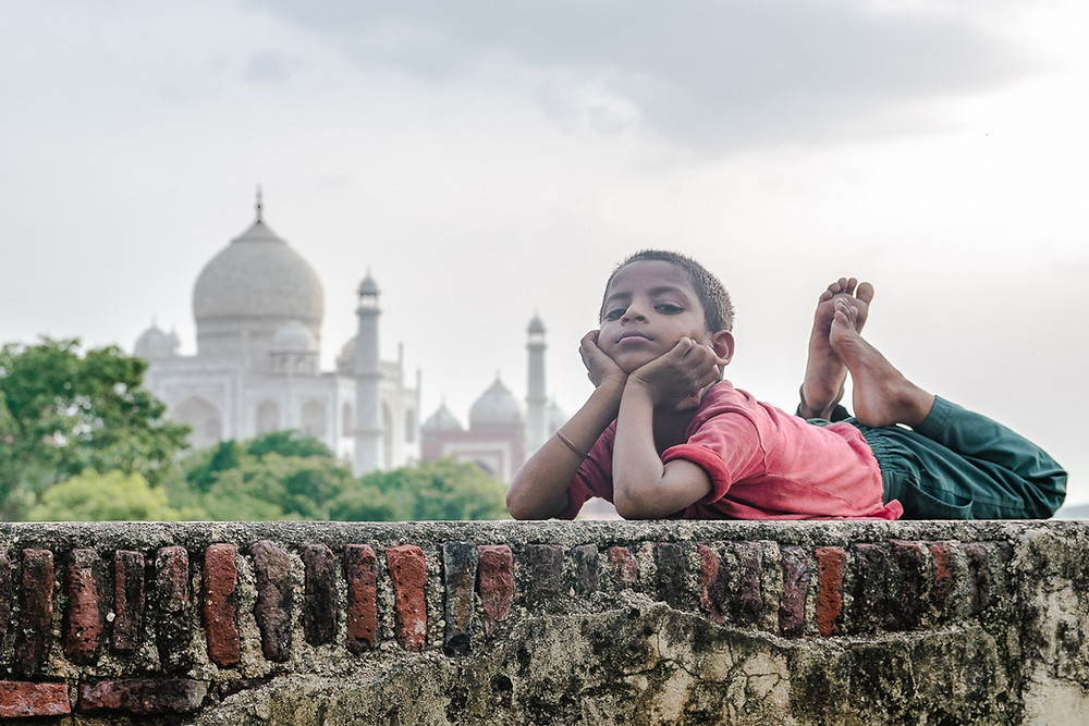 small indian boy lies on wall in front of the taj mahal in agra india
