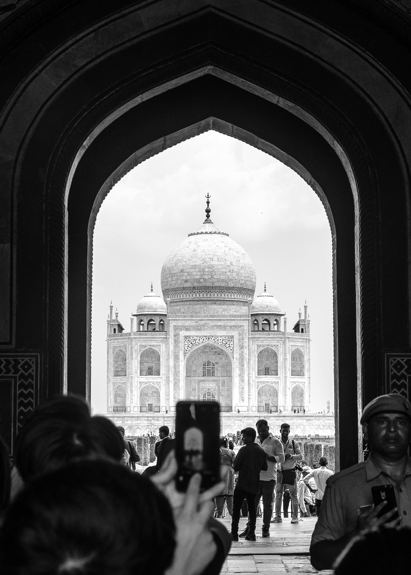 entrance to taj mahal showing crowds and people taking photos with phone