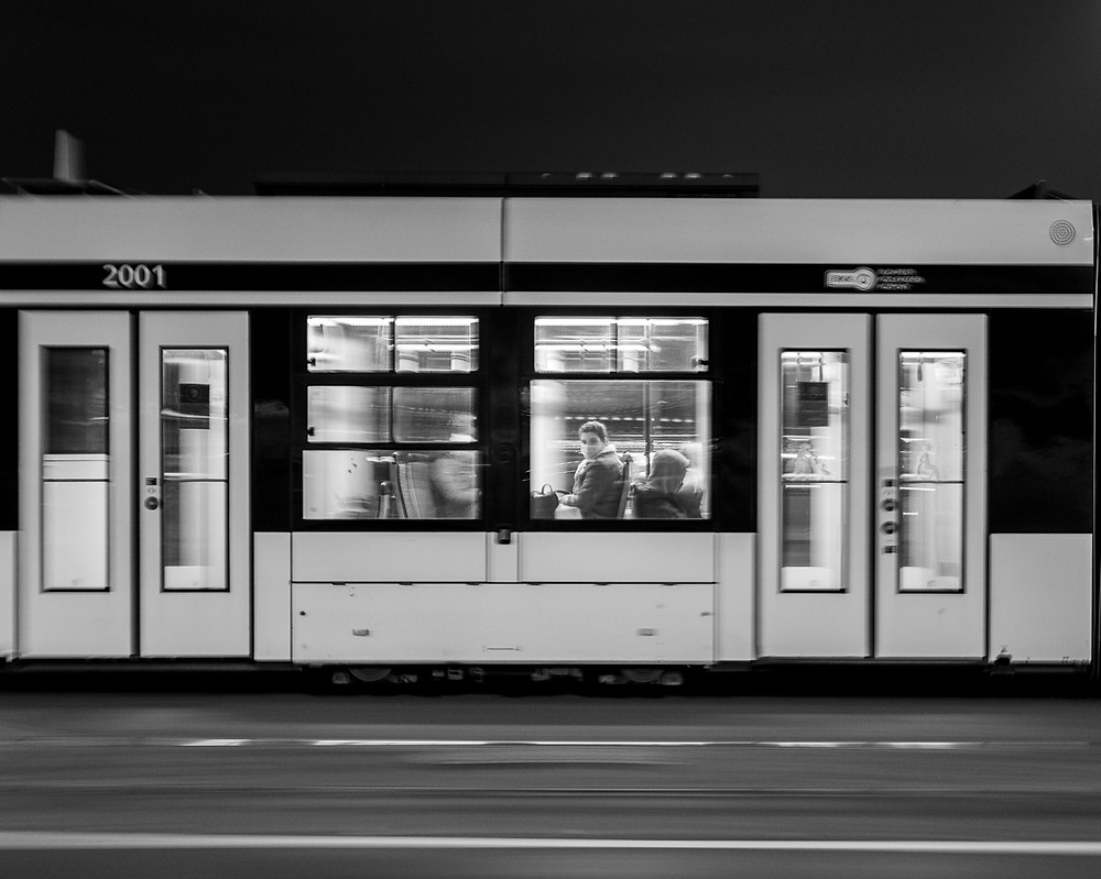Long exposure black and white photo of man on blurred out tram in Budapest