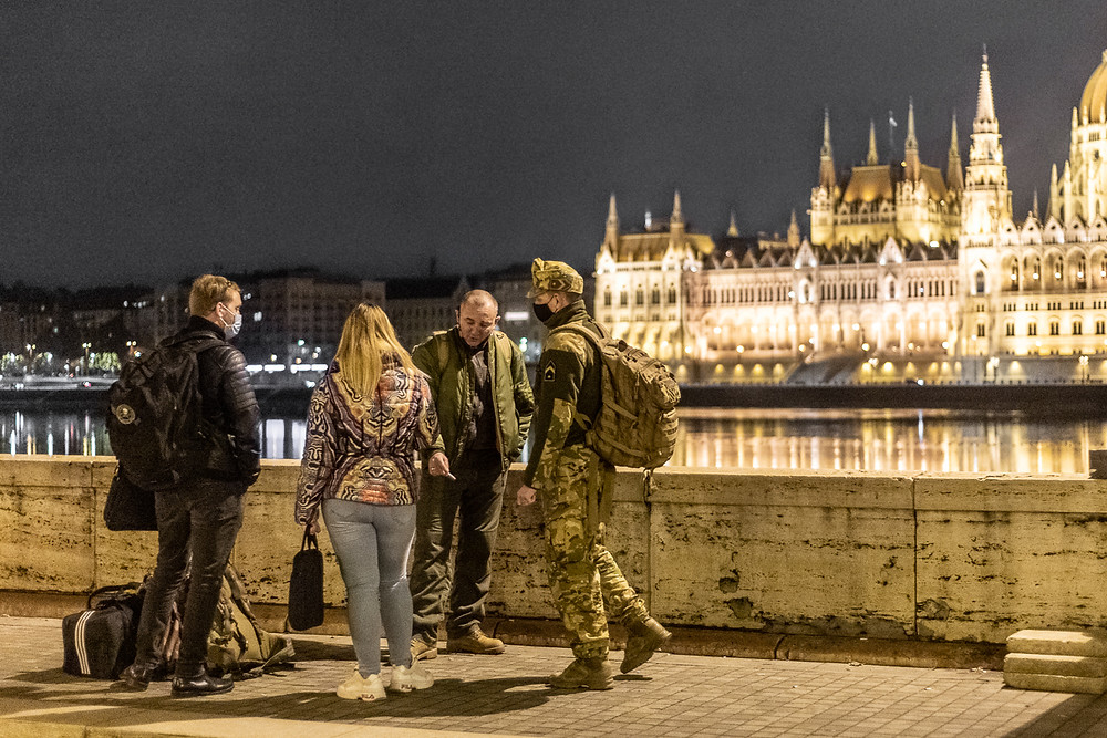 People meet their military friends next to the Danube river in Budapest, overlooking the houses of parliament