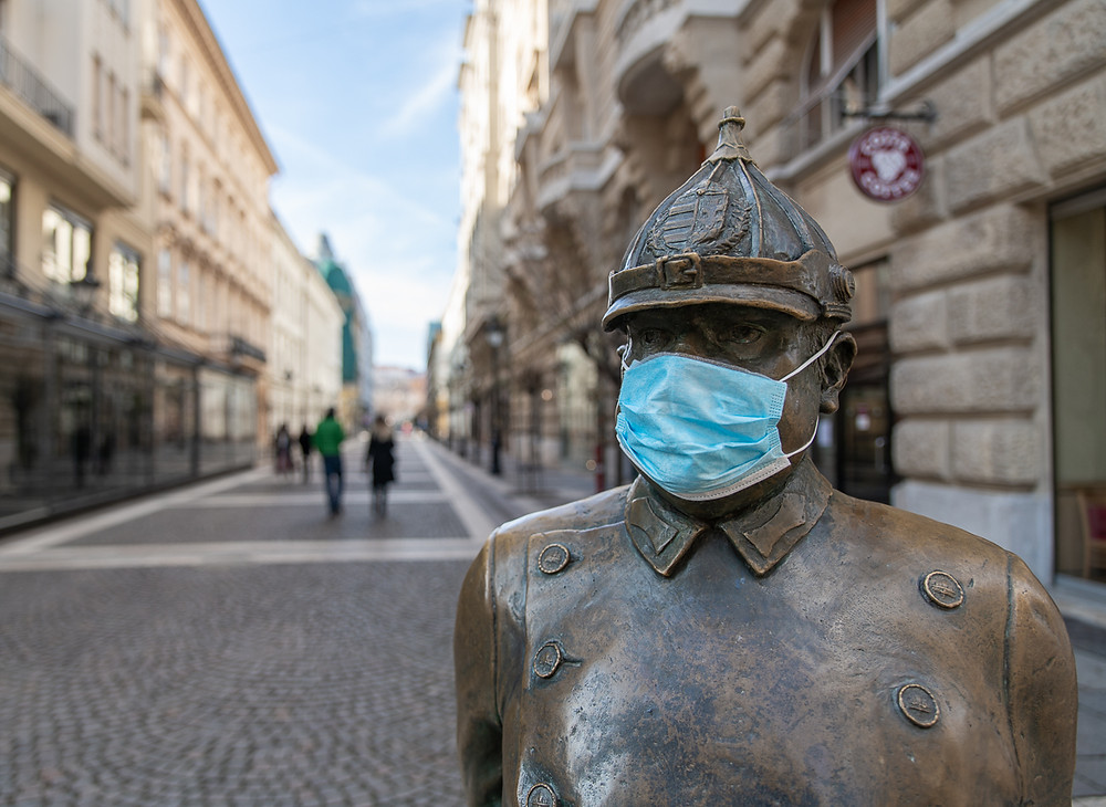 Bronze statue in Budapest with COVID-19 face mask