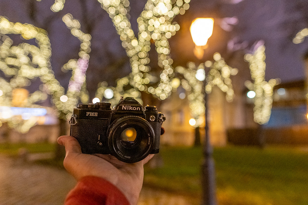 Nikon FM2 film camera held by Christmas lights in Budapest