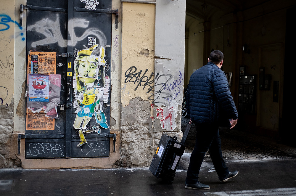 Man with suitcase walks past graffiti and art posters in Budapest