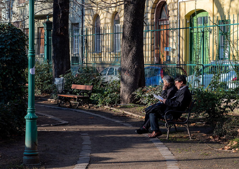 Old Asian couple sit on park bench in Budapest