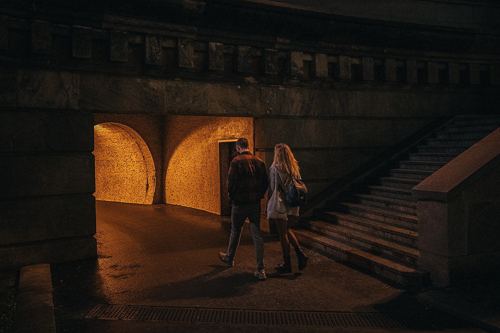 A couple walks into a tunnel underneath the chain bridge in Budapest