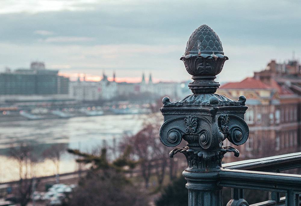 Sunrise next to ornate gate at the castle district in Budapest