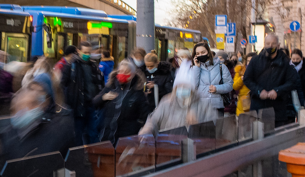 Long exposure of people in COVID-19 face masks leaving crowded bus in Budapest