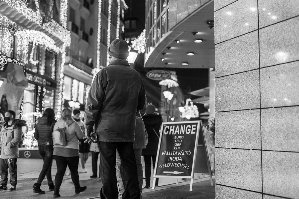 """Black and white street photo of man standing by sign that says """"Change"""""""