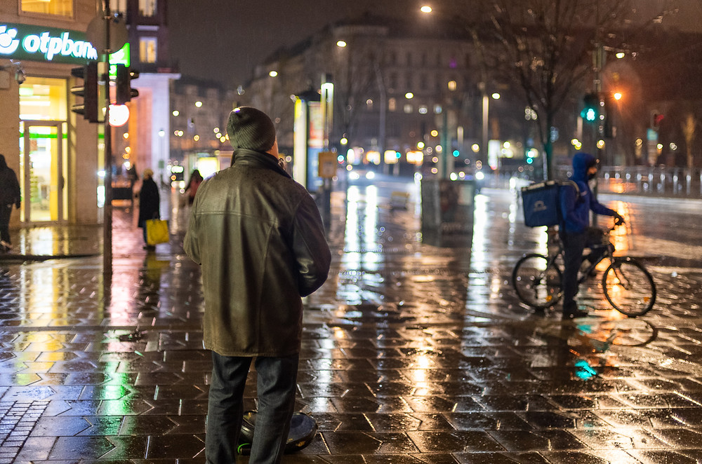 Man standing on ground with water reflecting street lights in Budapest