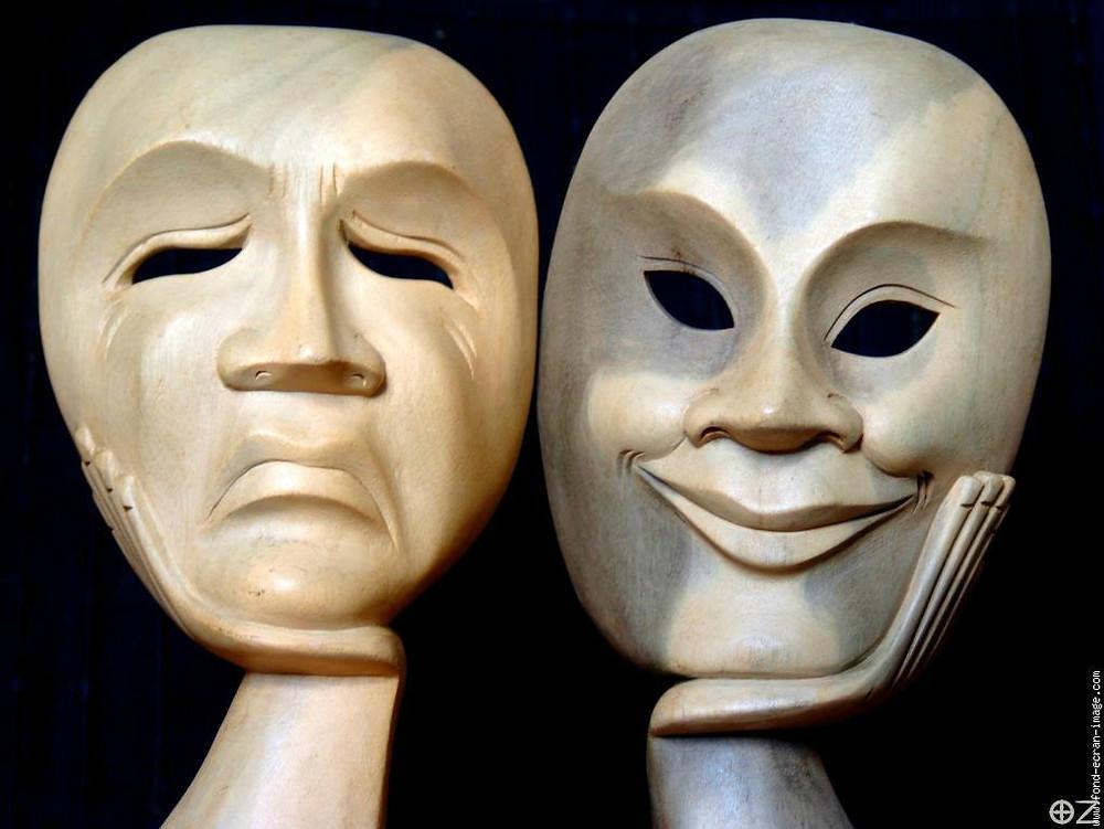 Photo de deux masques, un qui est triste et un qui sourit