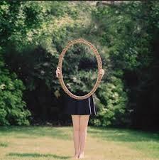 Femme qui porte un miroir derrière lequel elle disparait