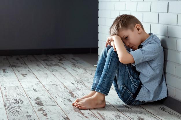 Photo d'un enfant seul assis au sol contre un mur