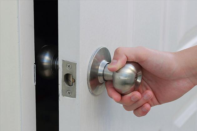 Photo d'une main qui actionne une poignée de porte