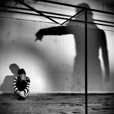 Photo d'une personne accroupie contre un mur, dominée par une ombre menaçante