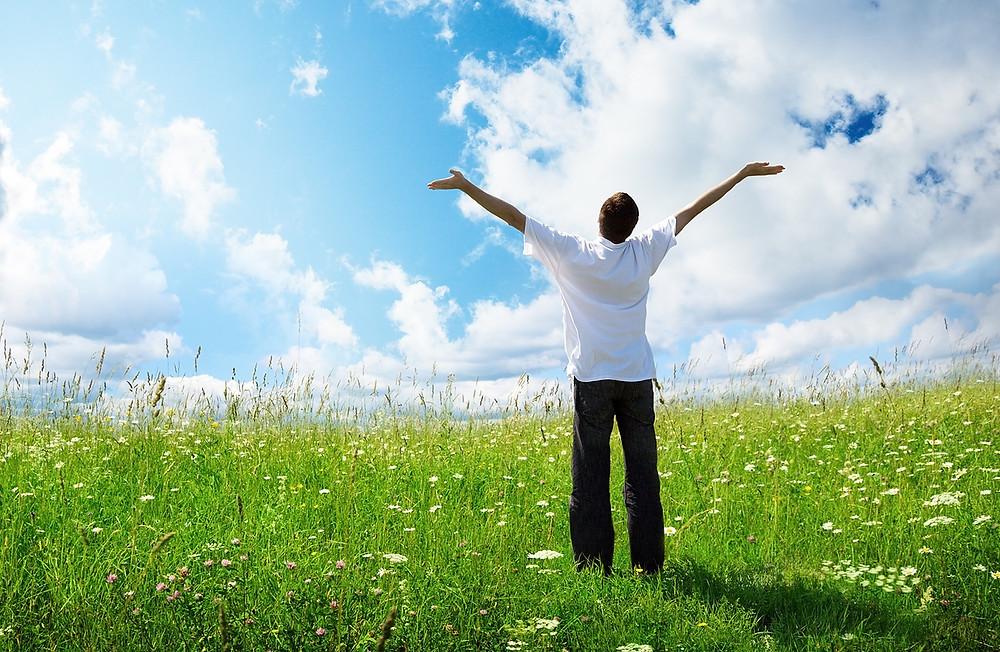 Photo d'une personne de dos bras levé au ciel, dans un paysage ensoleillé