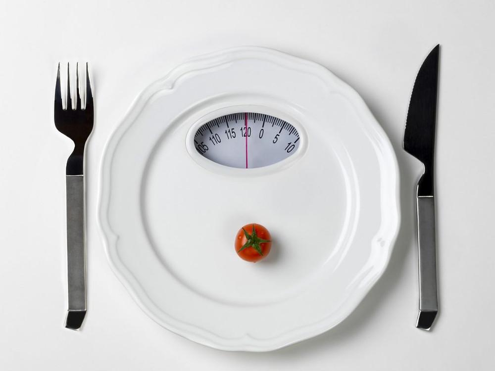 Photo d'une assiette transformée en pèse-personne et encadrée de couverts
