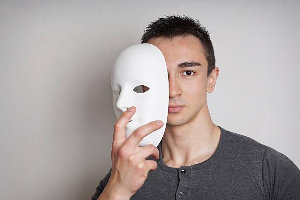 Homme qui enlève son masque de théatre