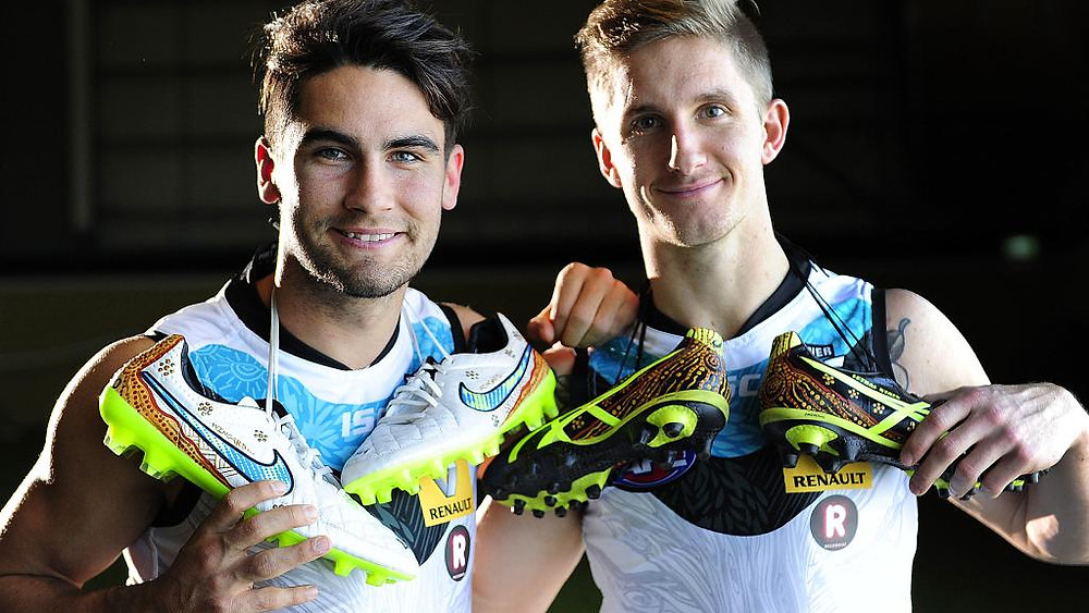 Chad Wingard and Hamish Hartlett with their boots painted by artist Shane Cook. Photo: Mark Brake.
