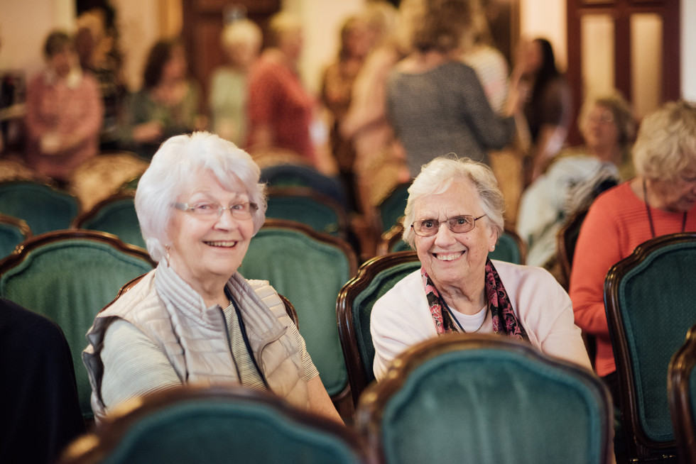 Two ladies sitting together, smiling at the camera.