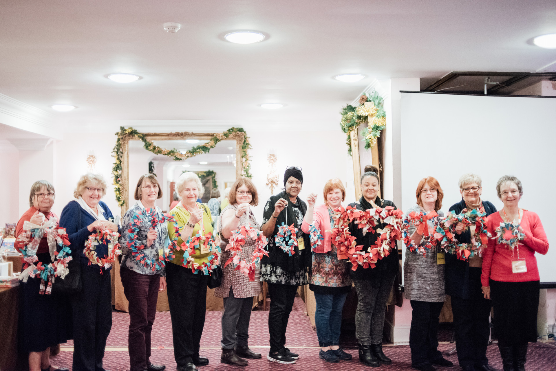 A line of eleven ladies each holding a handmade wreath and smiling.