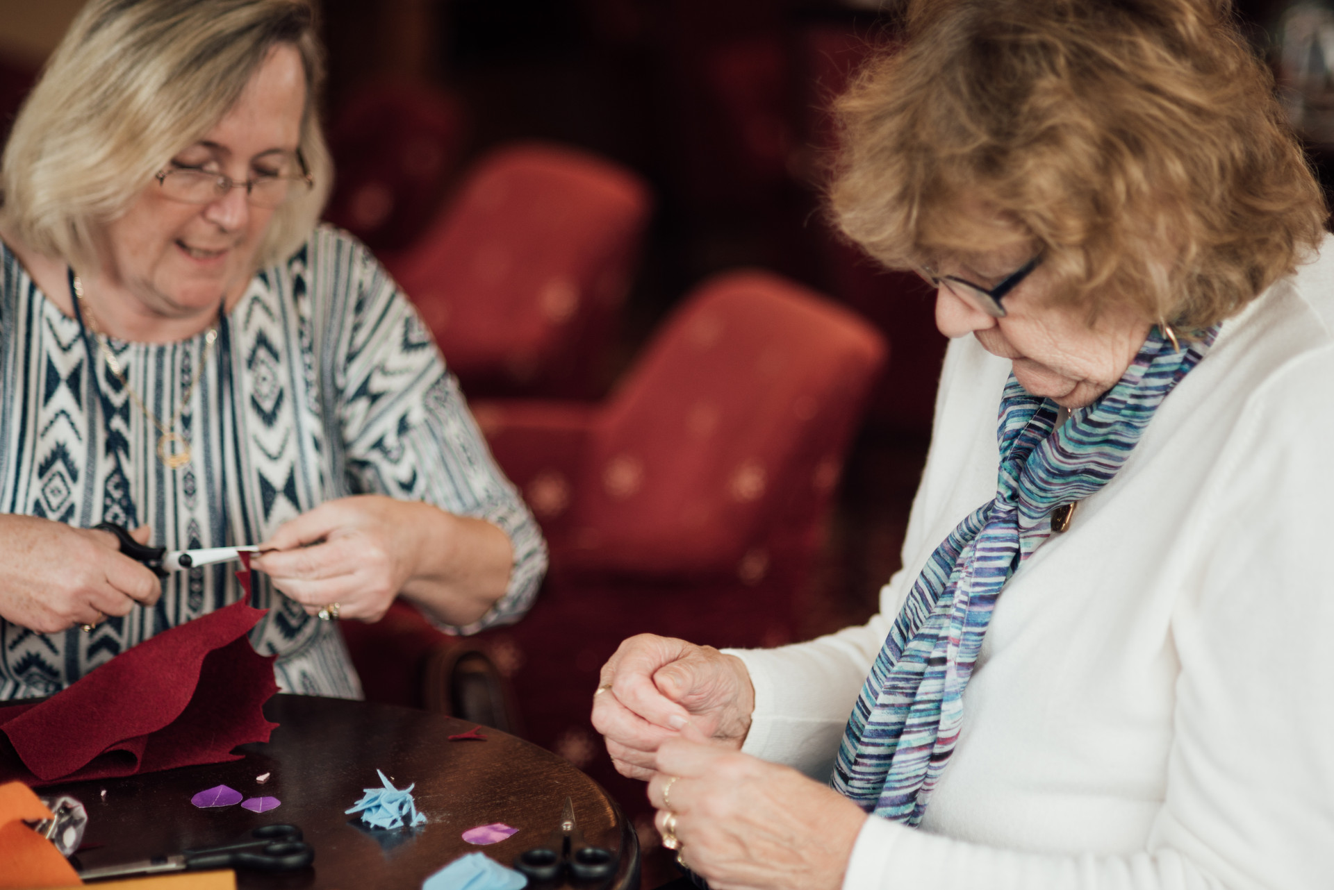 Two ladies smiling and cutting fabric in a craft activity.