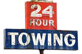Towing sign at a repair shop along Inter