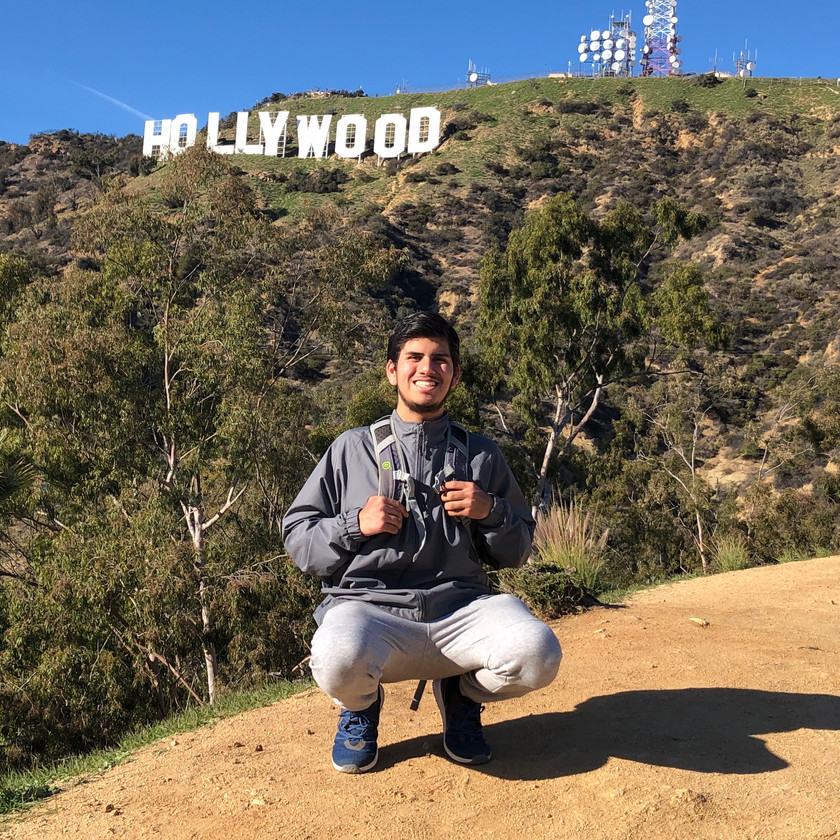 Latinx queer man squatting outdoors on hike, smiling at camera, with short brown hair, and short beard. He's wearing athletic wear with backpack, with the Hollywood sign behind him.