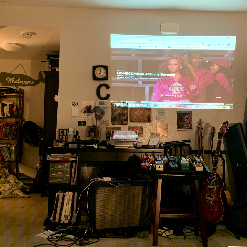 Projected still image of Beyonce's Homecoming Netflix special, above guitars, gear and a desk.
