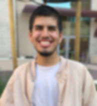 inx queer male seated and smiling at camera, with short brown hair, and short beard, he's wearing a white shirt and tan jacket with his hands in his pockets in front of university building.