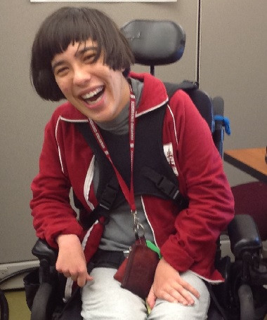 Lady smiling with short brown hair, in a red jacket, gray shirt, and in a motorized chair.