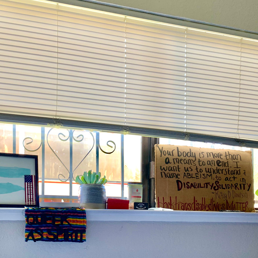 """Photo of Allie's windowsill that has a painting of two whales, a tapestry that says """"queer as spirit"""", two plants and a cardboard sign that says """"'Your body is more than a means to an end. I want us to understand & name ABLEISM, to act in DisabilitySolidarity' - Ki'tay D. Davidson #BlackTransDisabledLivesMatter"""""""