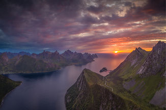 A stunning fjord viewpoint overlooking ocean and mountains during sunset.
