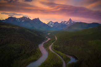 A River and road lead through a forest to giant mountains with soft clouds during sunset