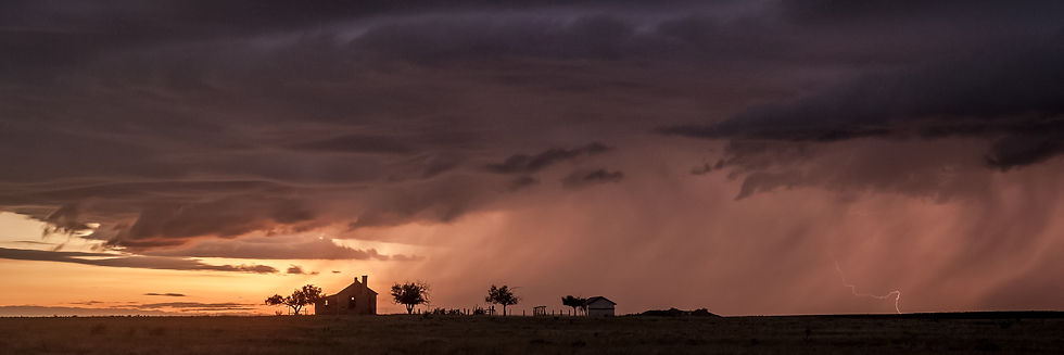 Old house and barn in open field during evening storm in Kim, Colorado