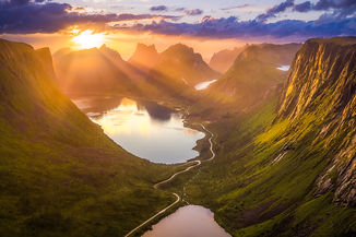 Bright sunrays shining through valley with 3 lakes and giant mountains in Norway