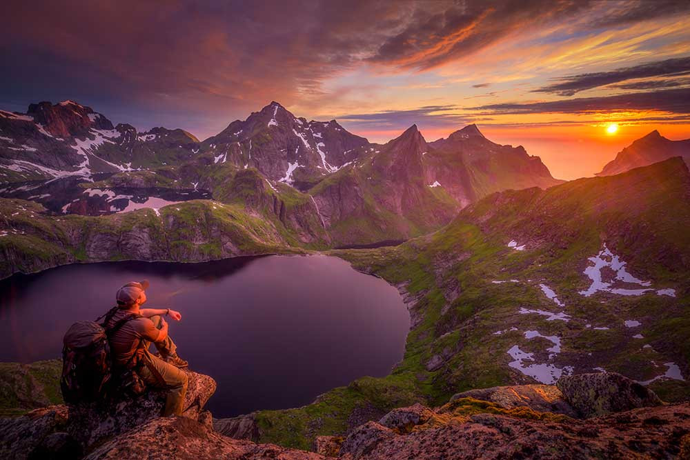 Man overlooking Norway fjords at sunset